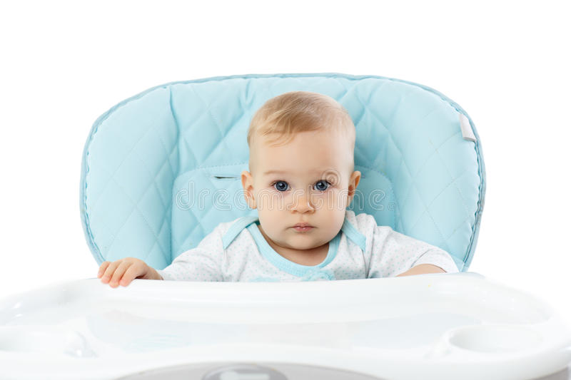 Sweet small girl sits in baby chair. Sweet small girl sits in baby chair on a white background stock image