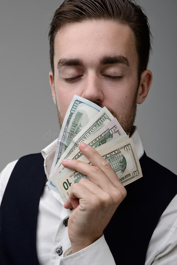 The sweet smell of money. A young man sniffing the money and dreams royalty free stock image