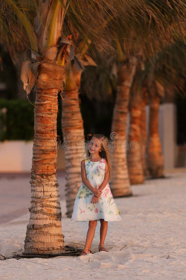 Sweet smiling girl near the palm trees on vacation stock images