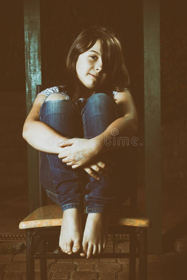 Cute young girl sitting in the dark on a chair stock image