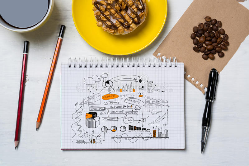 Sweet snack for new idea. Notepad with idea sketches coffee cup and pencil on wooden table royalty free stock image