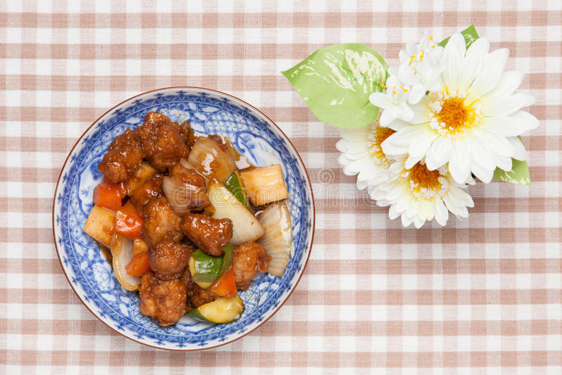 Sweet and sour pork and white artificial flowers stock photos
