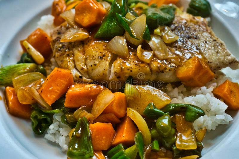 Sweet-sour vegetables in Chinese style with a light starch flour sauce on steamed cod on rice royalty free stock photo