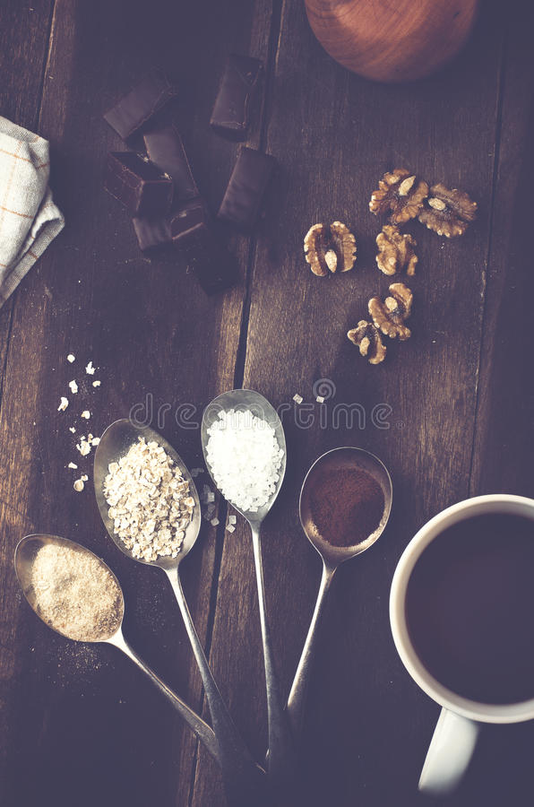 Sweet spices in the spoons and chocolate, nuts on a real brown w royalty free stock photography