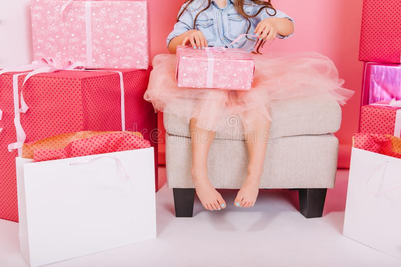 Sweet stylish image of birthday present opening by little child in tulle skirt suround big giftboxes on white floor. Brightful celebration of happy birthday stock photography