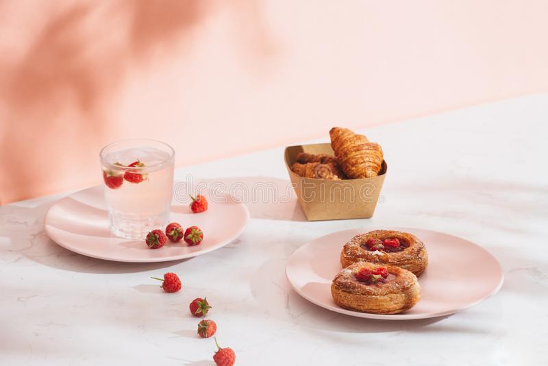Sweet summer dessert, homemade baked mini croissants, served with cold raspberry cider, fresh raspberries. On a white marble table. Copy space top view stock photo