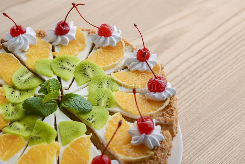 Sweet summer fruit cake with slices of orange, kiwi, cherries. frosting and whipped cream on top stock image