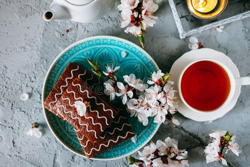 Sweet sunday dessert. Chocolate brownies with black tea. On table decorated with flowers and candles royalty free stock photo