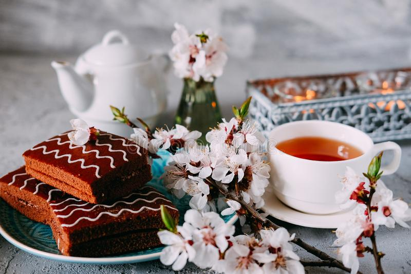 Sweet sunday dessert. Chocolate brownies with black tea. On table decorated with flowers and candles royalty free stock photography