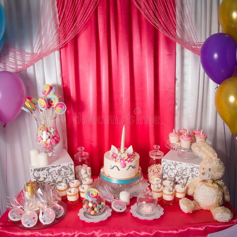 Sweet table and big unicorn cake for baby girl first birthday. Candy bar with a lot of different candies and sweet cakes.  stock photography