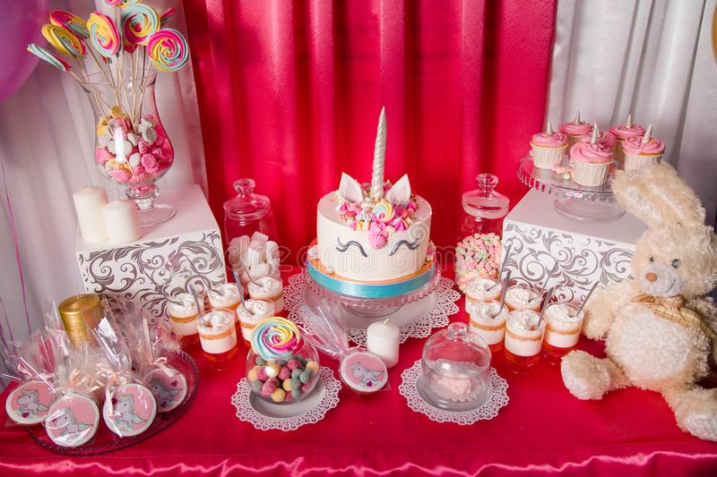 Sweet table and big unicorn cake for baby girl first birthday. Candy bar with a lot of different candies and sweet cakes.  royalty free stock photos