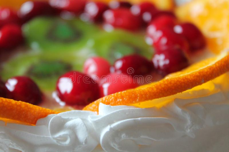 Sweet tasty cake with cream, fresh fruit and jelly. Delicious dessert with red berries, orange and kiwi slices. Template for cookbook, menu, postcard, website stock image