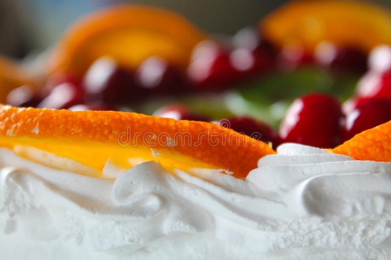 Sweet tasty cake with cream, fresh fruit and jelly. Delicious dessert with red berries, orange and kiwi slices. Template for cookbook, menu, postcard, website royalty free stock photo