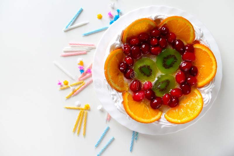 Sweet tasty cake with cream, fresh fruit and jelly. Twisted candles scattered around. Dessert with red berries, kiwi and orange slices. Greeting card template stock images