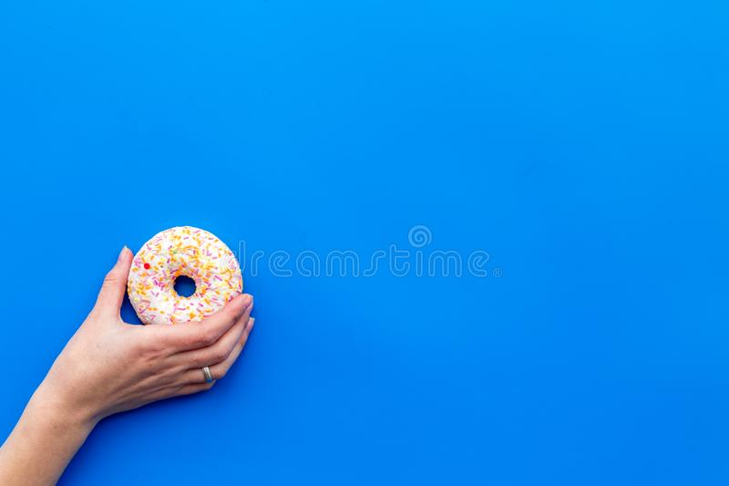 Sweet tasty snack. Glazed donut on blue background top view copy space stock photography