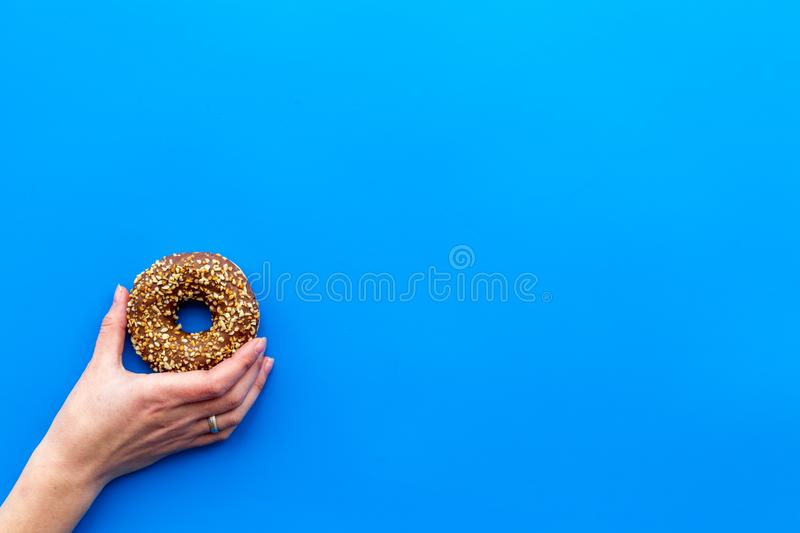 Sweet tasty snack. Glazed donut on blue background top view copy space stock image
