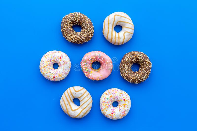 Sweet tasty snack. Glazed donut on blue background top view copy space stock photo