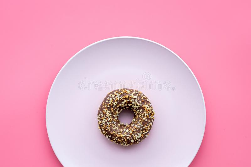Sweet tasty snack. Glazed donut on plate on pink background top view copy space stock image