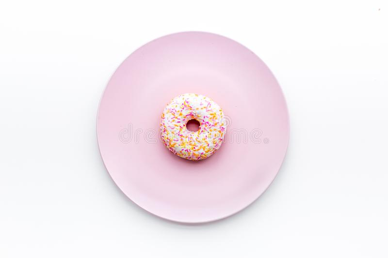 Sweet tasty snack. Glazed donut on plate on white background top view copy space stock photo