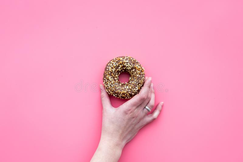 Sweet tasty snack. Hand hold glazed donut on pink background top view copy space royalty free stock photography