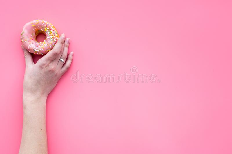 Sweet tasty snack. Hand hold glazed donut on pink background top view copy space royalty free stock image