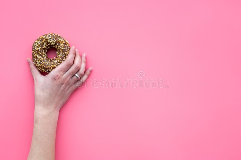 Sweet tasty snack. Hand hold glazed donut on pink background top view copy space royalty free stock photos