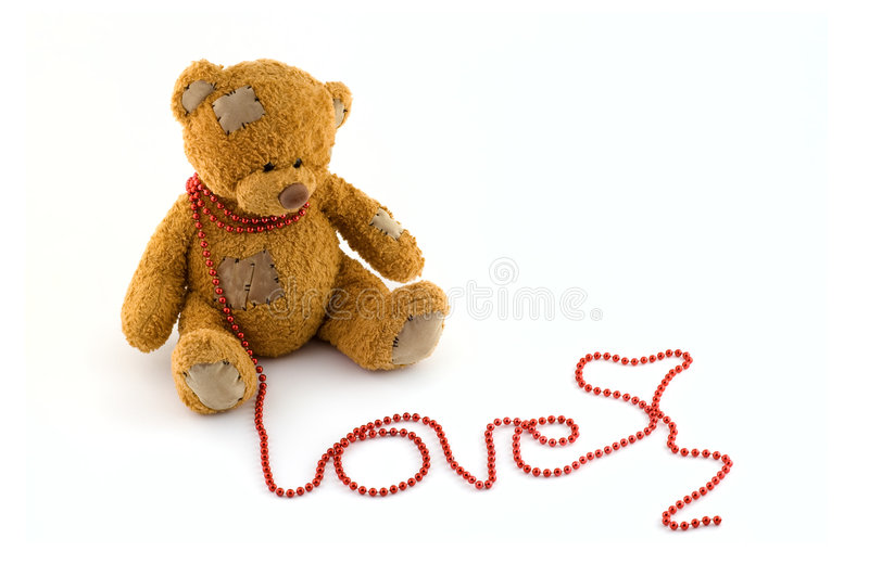 Sweet teddy bear with a string of red beads royalty free stock images