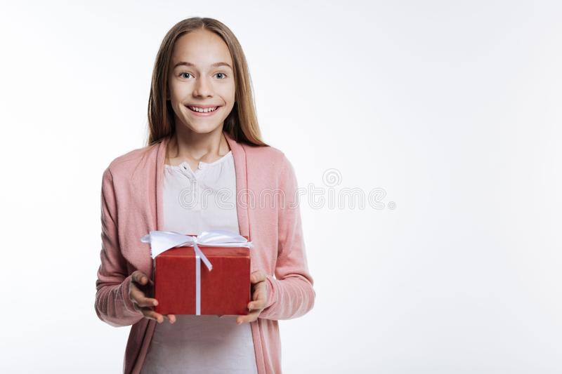 Sweet teenage girl holding a gift box royalty free stock images