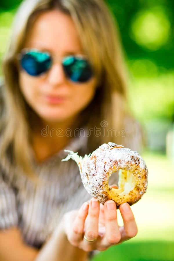 Sweet temptation, woman is showing piece of Trdelnik stock image