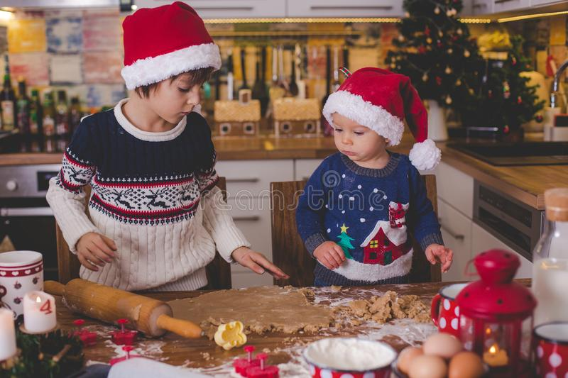 Sweet toddler child and his older brother, boys, helping mommy p royalty free stock images