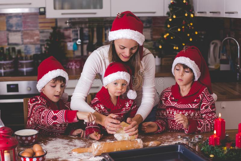 Sweet toddler child and his older brother, boys, helping mommy preparing Christmas cookies at home stock photo