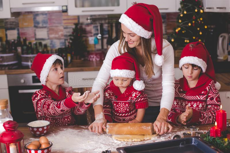Sweet toddler child and his older brother, boys, helping mommy preparing Christmas cookies at home stock photography