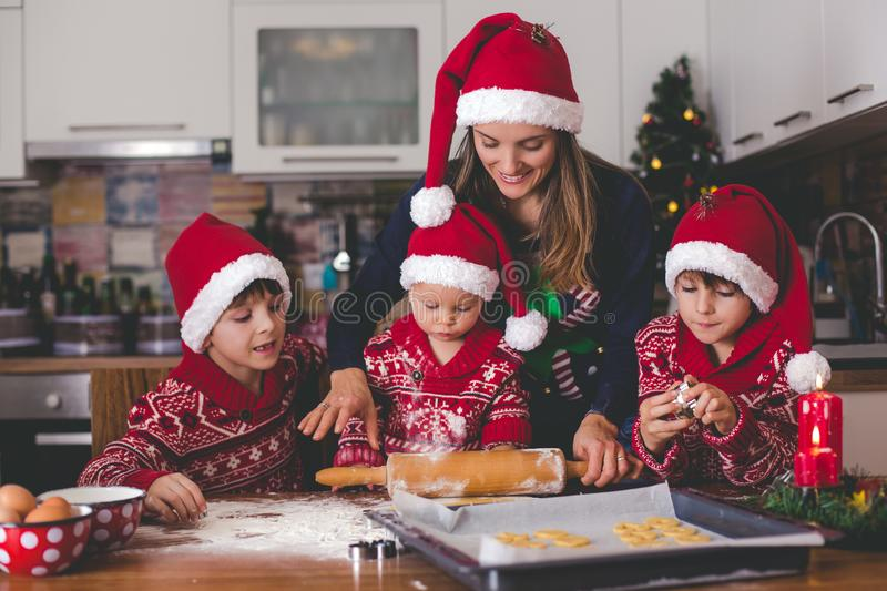 Sweet toddler child and his older brother, boys, helping mommy preparing Christmas cookies at home royalty free stock photo
