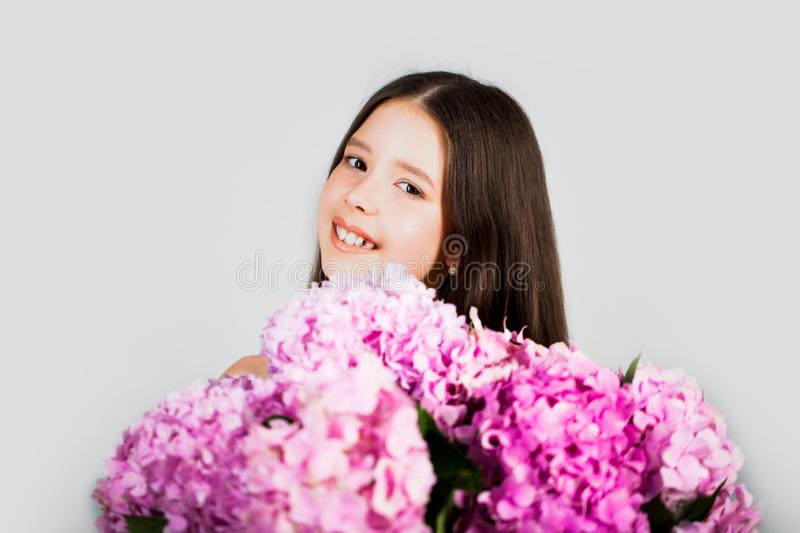 Sweet toddler girl with floral on and flowers bunch in hands. Child. Childhood. Kids. Portrait of a smiling little girl royalty free stock photo