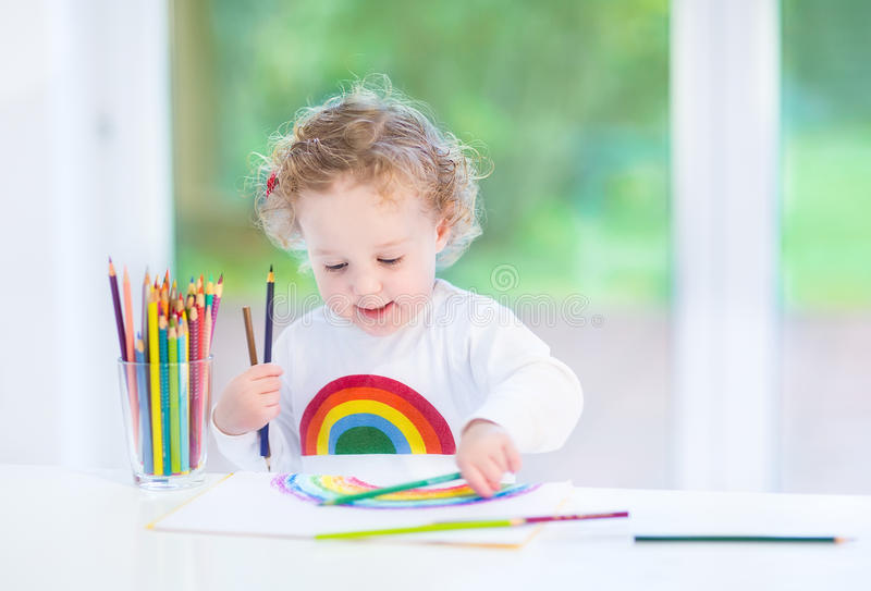 Sweet toddler girl painting rainbow in white room stock photo