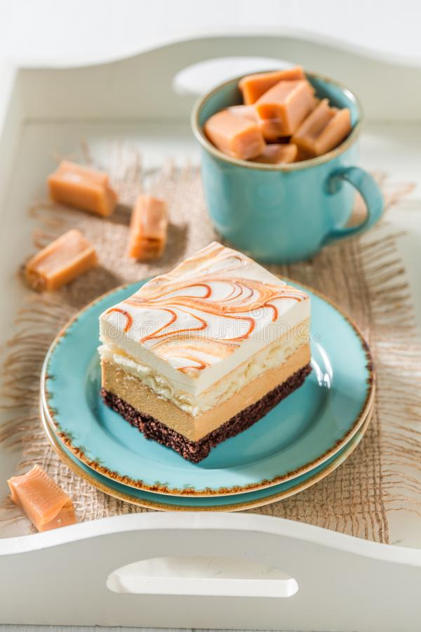 Sweet toffee cake on blue porcelain with fudge bars. On white background stock photos