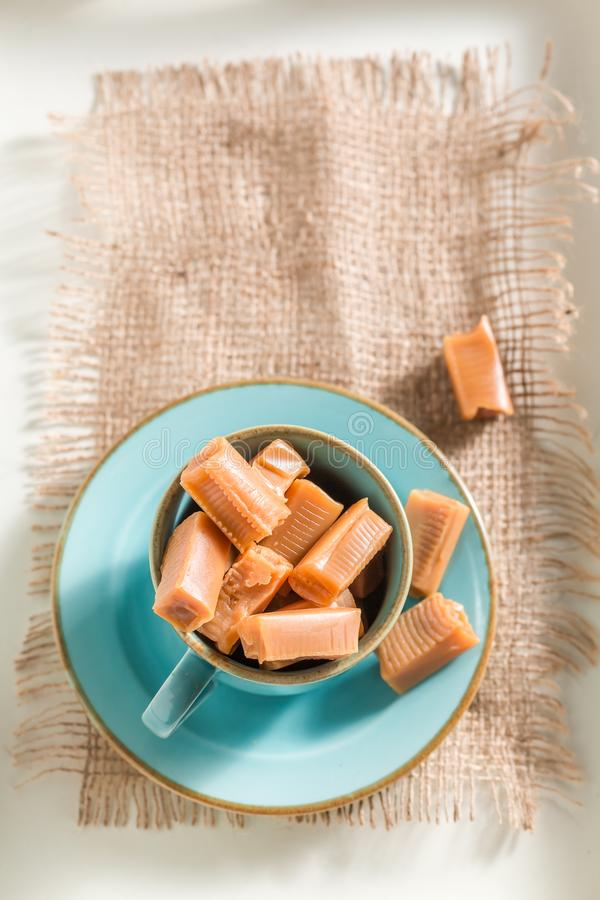 Sweet toffee cake with fudge bars on blue porcelain. On white background stock image