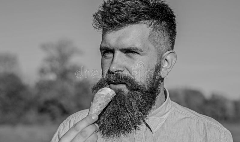 Sweet tooth concept. Bearded man with ice cream cone. Man with beard and mustache on calm face eats ice cream, bite. Waffle cone, blue sky background, defocused royalty free stock photos
