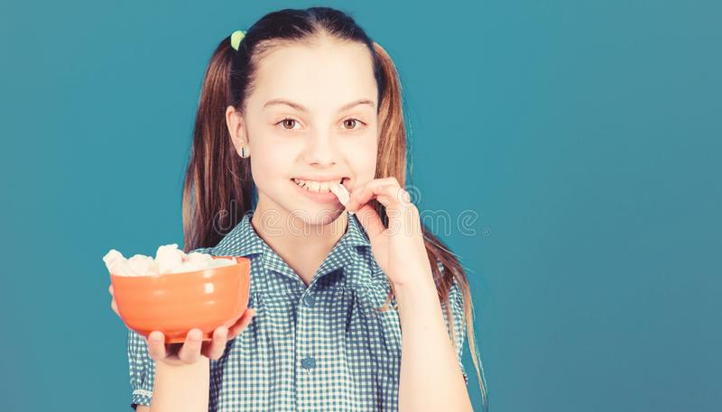 Sweet tooth concept. Calorie and diet. Girl smiling face hold bowl sweet marshmallows in hand blue background. Kid girl royalty free stock photo