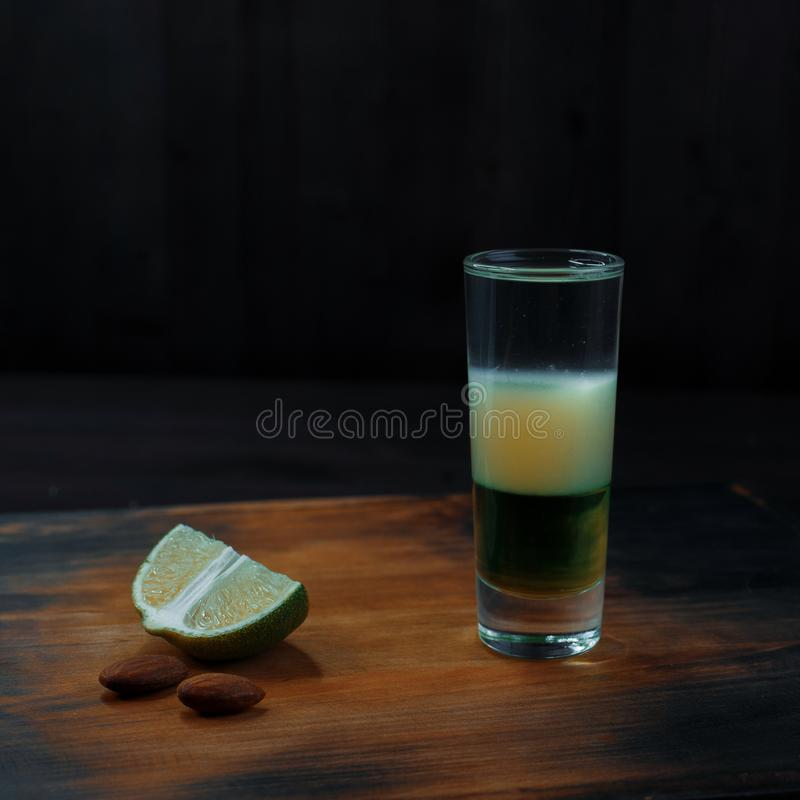 Sweet two-layer cocktail with pear syrup and coconut syrup stands on an old wooden table next to a slice of lime. Alcoholic cocktail shot. Night club life stock photography
