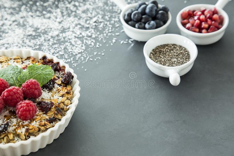 Sweet vegan dessert from seeds and summer fruit and blurry background with ingredients for a tart. Sweet vegan dessert of seeds and summer fruit as well as a royalty free stock photo