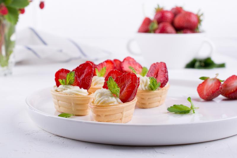 Sweet waffle basket with cream cheese and strawberries for summer breakfast. Over white background royalty free stock photo