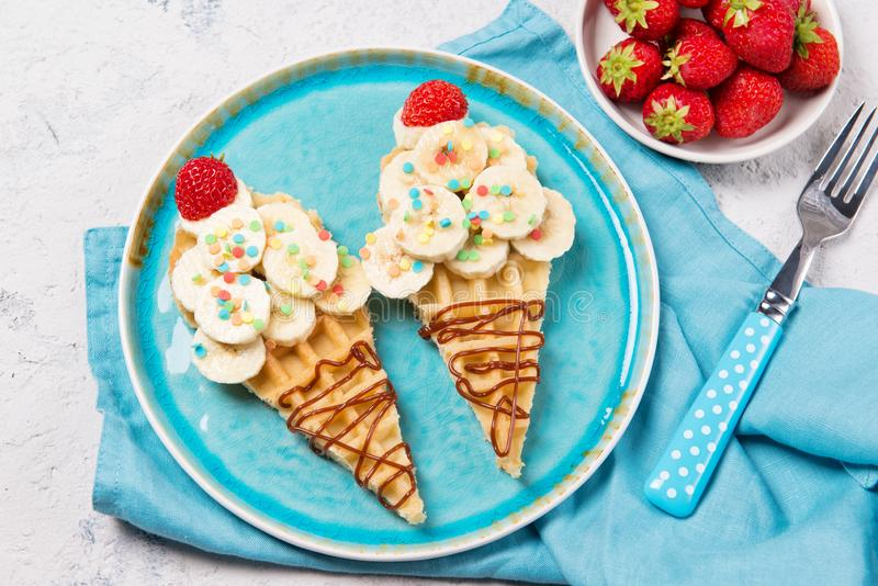 Sweet waffles with banana and strawberry in a shape of ice cream cone, meal for kids idea, top view stock photo