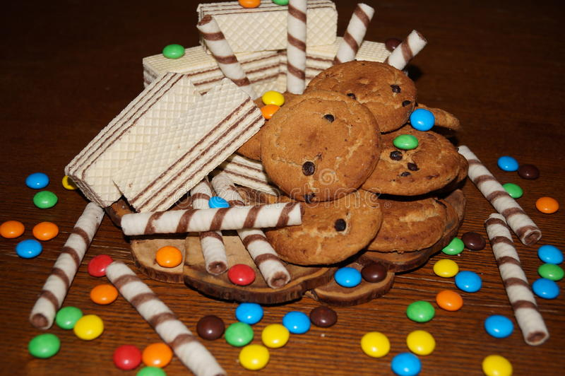 Sweet waffles, biscuits, candies. On a wooden table stock photos
