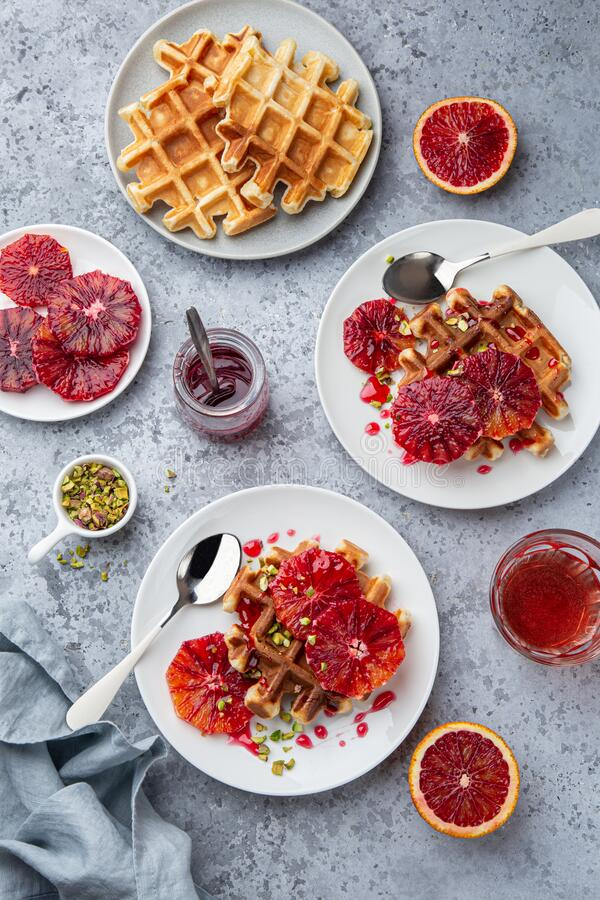Sweet waffles with red blood oranges and pistachios nuts stock image