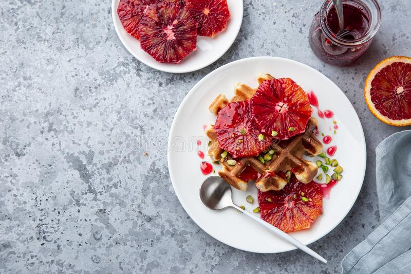 Sweet waffles with red blood oranges and pistachios nuts royalty free stock photography
