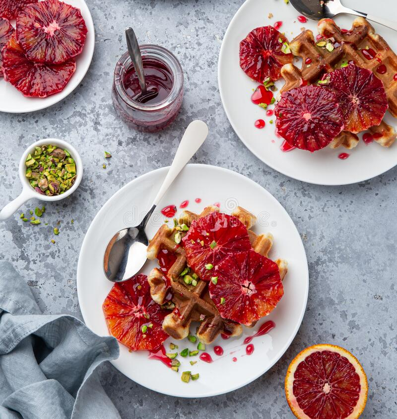 Sweet waffles with red blood oranges and pistachios nuts royalty free stock photo