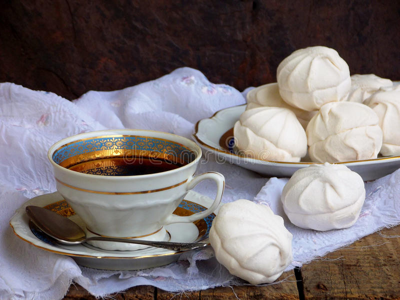 Sweet white Russian marshmallow, chocolate zephyr, meringue and cup of coffee on wooden background. royalty free stock photos
