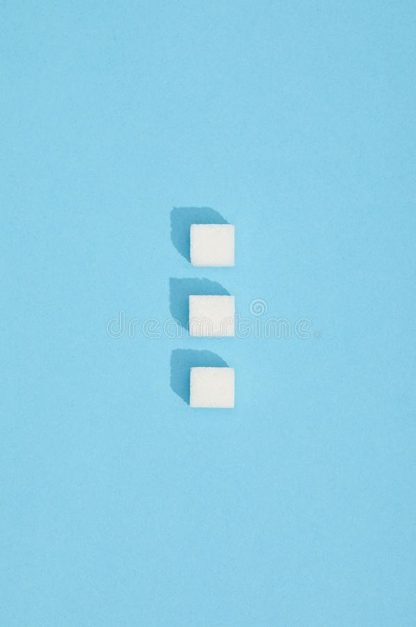 Sweet white sugar cubes with shadows on blue royalty free stock photo