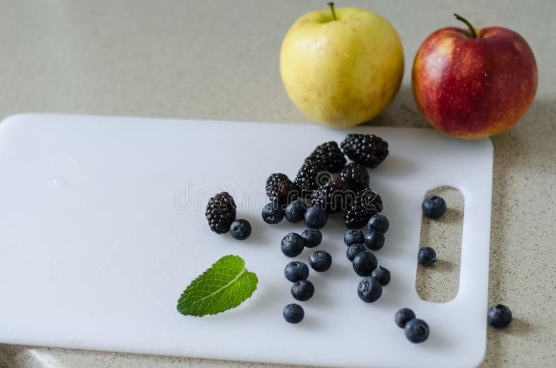 Sweet whole apples, blueberries, blackberries and mint leaves around, fresh summer fruits stock photo